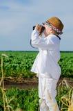 Kleiner Junge, der im Ackerland unter Verwendung der Ferngläser steht Lizenzfreie Stockfotos