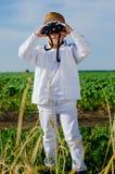 Kleiner Junge, der im Ackerland unter Verwendung der Ferngläser steht Lizenzfreie Stockbilder