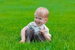 Kleiner Junge, der im grünen Gras sitzt und träumt Lizenzfreie Stockfotos