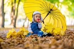 Kleiner Junge, der im Herbstpark mit einem Regenschirm sitzt und einen Apfel isst Lizenzfreie Stockfotos