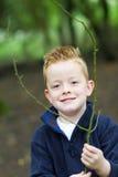 Kleiner Junge, der im Holz lächelt Stockfotografie
