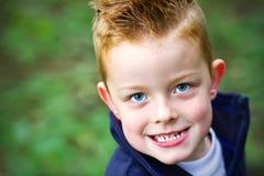 Kleiner Junge, der im Holz lächelt Stockfoto