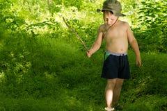 Kleiner Junge, der im Holz mit einem Stock spielt Stockfotografie