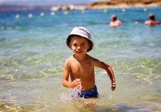 Kleiner Junge, der im Meer/im Ozean spielt Stockfotos