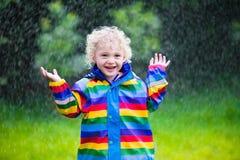 Kleiner Junge, der im Regen spielt Stockfoto