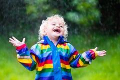 Kleiner Junge, der im Regen spielt Stockbild