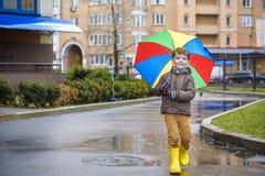 Kleiner Junge, der im regnerischen Sommerpark spielt Kind mit dem bunten Regenbogenregenschirm, wasserdichtem Mantel und den Stie lizenzfreie stockbilder