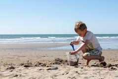 Kleiner Junge, der im Sand auf dem Strand spielt Lizenzfreie Stockbilder