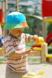 Kleiner Junge, der im Sandkasten spielt Lizenzfreie Stockbilder