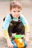 Kleiner Junge, der im Spielzeugauto spielt Stockfotos