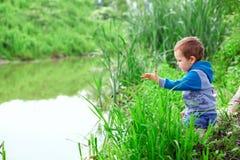 Kleiner Junge, der im Stock auf Flussufer, werfende Steine sitzt Stockfotos