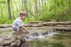 Kleiner Junge, der im Wasserfall spielt lizenzfreie stockbilder