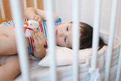 Kleiner Junge, der im weißen Bett liegt Stockfoto