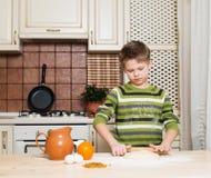 Kleiner Junge in der Küche, die den Teig für Plätzchen unter Verwendung des Rollens zubereitet. Lizenzfreie Stockfotos