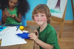 Kleiner Junge, der Künste und Handwerksversorgungen verwendet Lizenzfreie Stockfotos