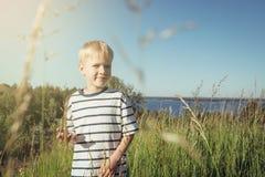 Kleiner Junge, der Kamera auf Natur lächelt und betrachtet Stockfoto