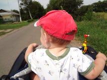 Kleiner Junge in der Kappe erforscht Straßenreiten Stockfoto