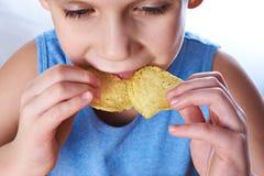 Kleiner Junge, der Kartoffelchips isst Stockbild