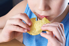 Kleiner Junge, der Kartoffelchips isst Stockfoto