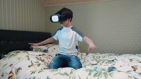 Kleiner Junge, der Kopfhörer der virtuellen Realität im Flugsimulator sitzt auf dem Bett verwendet stock video footage