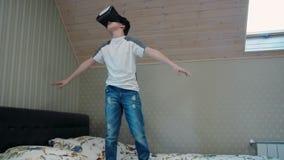 Kleiner Junge, der Kopfhörer der virtuellen Realität im Flugsimulator steht auf dem Bett verwendet stock video