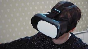Kleiner Junge, der Kopfhörer der virtuellen Realität im Flugsimulator verwendet stock video footage