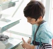 Kleiner Junge, der Kuchen am Bäckereishop vorwählt Stockfotos