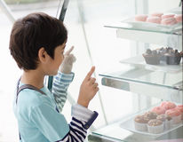 Kleiner Junge, der Kuchen am Bäckereishop vorwählt Stockbilder