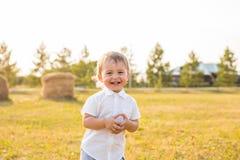 Kleiner Junge in der Landschaft Kleinkind, das draußen aktive Spiele spielt Kindheit, sorglos, Kinderspiele, Junge, frisch Lizenzfreie Stockfotos