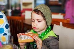 Kleiner Junge, der Lebkuchen isst Stockfotos
