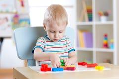 Kleiner Junge, der lernt, bunten Spielteig im Kindertagesstättenraum zu benutzen Lizenzfreies Stockfoto