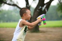 Kleiner Junge, der Luftblasengewehr spielt Stockfotos