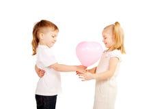 Kleiner Junge, der Mädchen ein Herz, Valentinstagkonzept gibt. Stockfotografie