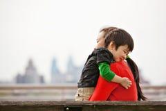 Kleiner Junge, der Mamma auf Bank umarmt Lizenzfreie Stockbilder