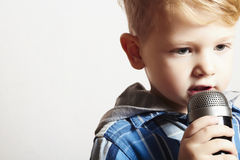 Kleiner Junge, der in microphone.child in karaoke.music singt Lizenzfreies Stockfoto