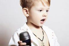 Kleiner Junge, der in microphone.child in karaoke.music singt stockfoto