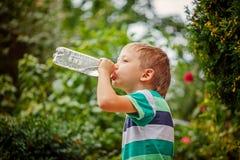 Kleiner Junge, der an Mineralwasser von der Plastikflasche heraus trinkt Lizenzfreie Stockfotos