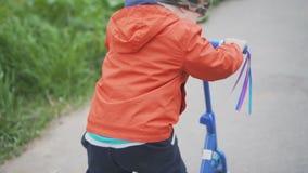Kleiner Junge, der Miniroller im Park am sonnigen Tag in der Zeitlupe reitet stock footage