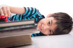 Kleiner Junge, der mit Autospielzeugfreizeit nach Studie spielt Stockfotos