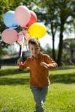 Kleiner Junge, der mit Ballonen läuft stockfotografie