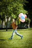 Kleiner Junge, der mit Ballonen läuft stockbilder