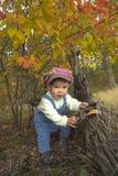 Kleiner Junge, der mit Blättern am Herbstpark spielt Stockfoto