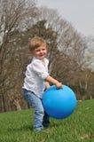Kleiner Junge, der mit blauem Ball spielt Stockfoto