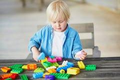 Kleiner Junge, der mit bunten Plastikbaublöcken spielt Stockfotos