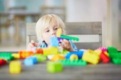 Kleiner Junge, der mit bunten Plastikbaublöcken spielt Lizenzfreie Stockbilder