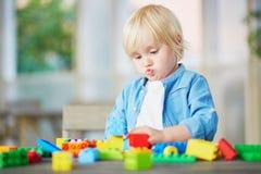 Kleiner Junge, der mit bunten Plastikbaublöcken spielt Stockfoto