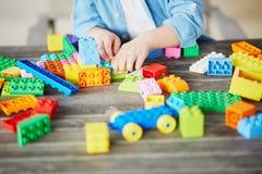 Kleiner Junge, der mit bunten Plastikbaublöcken spielt Lizenzfreies Stockbild
