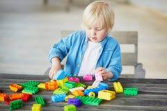Kleiner Junge, der mit bunten Plastikbaublöcken spielt Lizenzfreie Stockfotografie