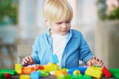 Kleiner Junge, der mit bunten Plastikbaublöcken spielt Stockbilder