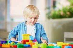 Kleiner Junge, der mit bunten Plastikbaublöcken spielt Lizenzfreie Stockfotos